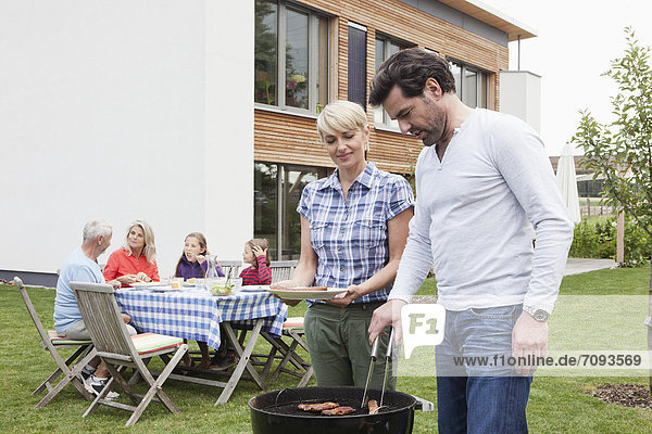 Germany  Bavaria  Nuremberg  Couple grilling barbecue  family sitting in background