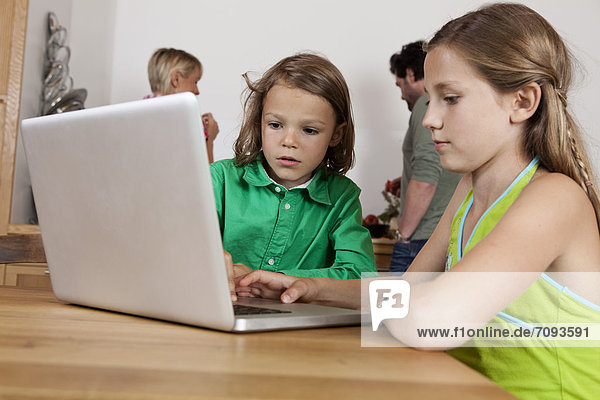 Girl and boy using laptop in kitchen