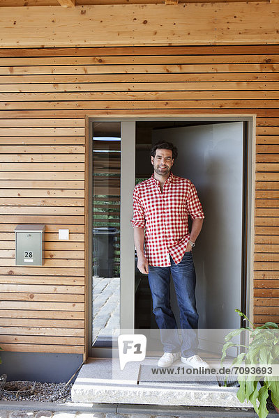 Mature man standing at front door of house