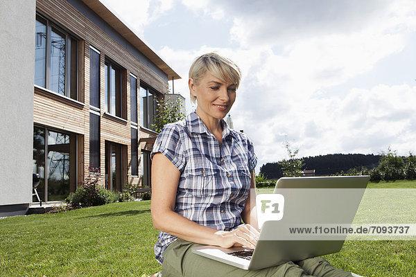 Reife Frau mit Laptop im Garten