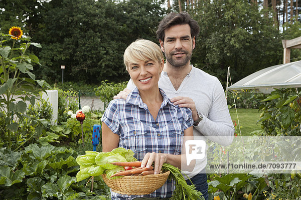 Germany  Bavaria  Nuremberg  Mature couple with vegetables in garden