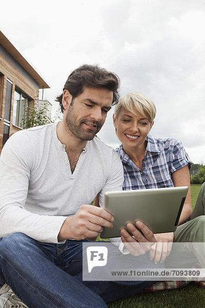 Germany  Bavaria  Nuremberg  Mature couple using digital tablet in garden