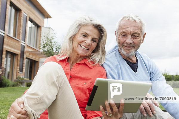 Deutschland  Bayern  Nürnberg  Seniorenpaar mit digitalem Tablett im Garten