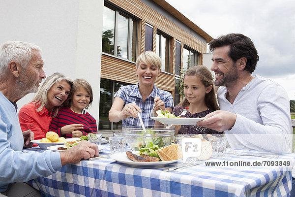 Germany  Bavaria  Nuremberg  Family having barbecue in garden