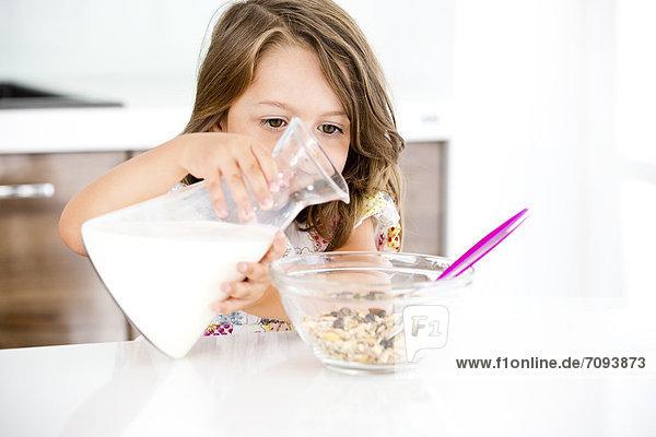 Deutschland  Mädchen gießt Milch ins Müsli
