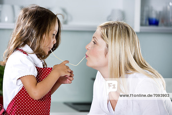 Deutschland,  Tochter isst Nudeln mit Mutter in der Küche