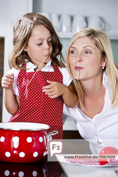 Deutschland  Mutter und Tochter essen Nudeln in der Küche