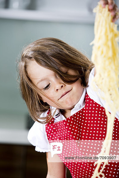 Germany,  Girl playing with spaghetti