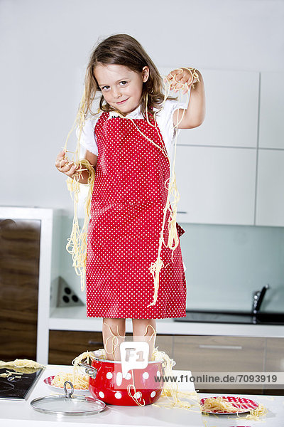 Germany  Girl playing with spaghetti on kitchen worktop