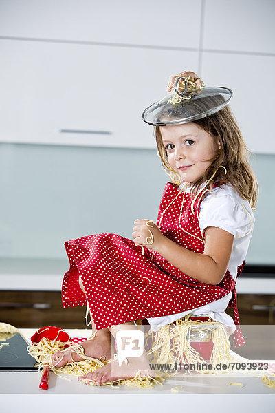 Deutschland  Mädchen spielt mit Spaghetti auf Küchenarbeitsplatte