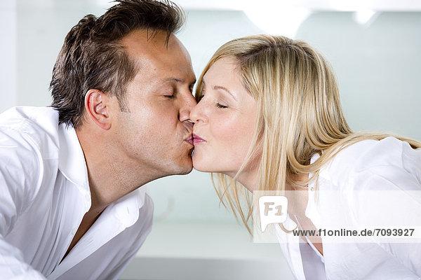 Deutschland  Mittleres erwachsenes Paar beim Nudelessen und Küssen