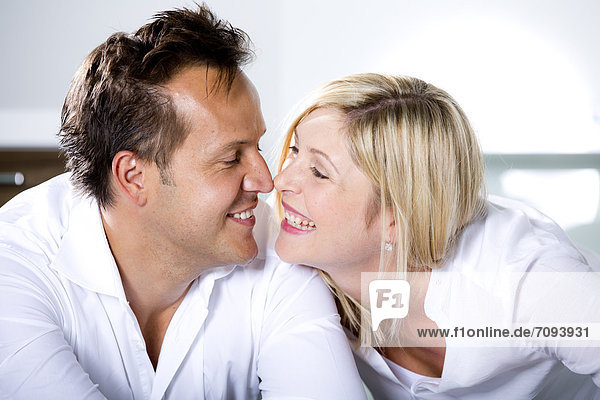 Germany  Mid adult couple touching nose  smiling