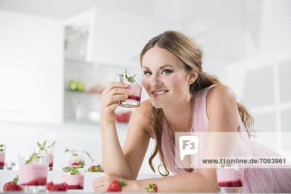 Deutschland  Junge Frau mit Joghurtglas  Portrait