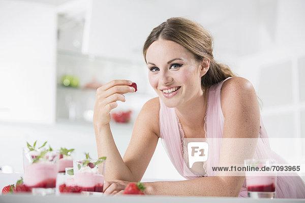 Deutschland  Junge Frau hält Erdbeere  lächelnd  Portrait