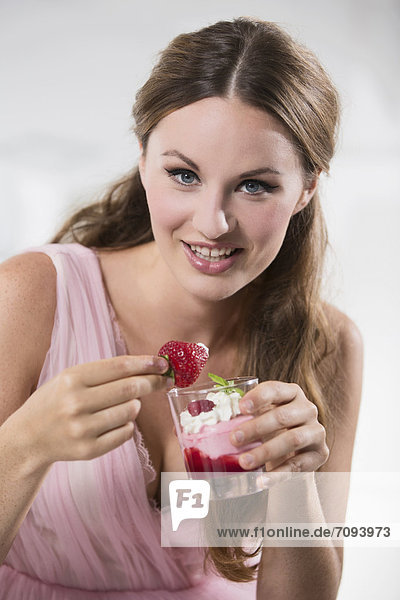 Germany  Young woman holding dipped strawberry in her hand  smiling  portrait