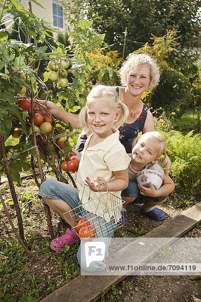 Germany  Bavaria  Grandmother with children in vegetable garden