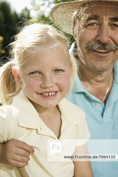 Germany  Bavaria  Grandfather and granddaughter smiling  portrait