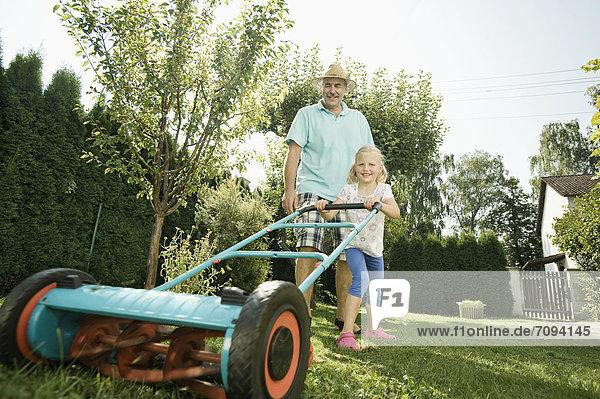 Deutschland  Bayern  Großvater mit Kindern beim Rasenmähen