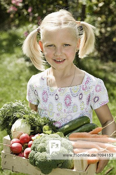 Girl holding vegetables in crate  smiling  portrait