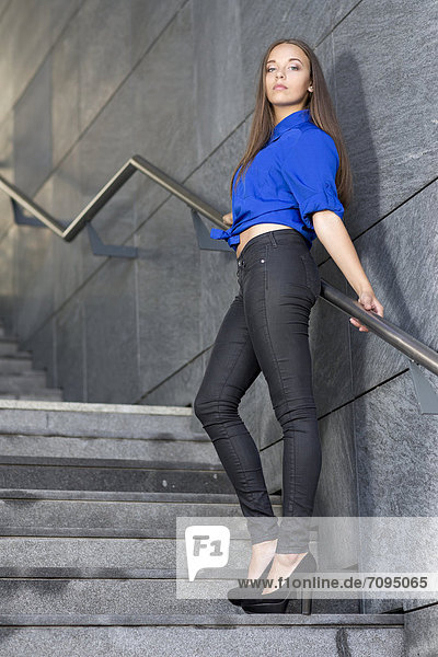 Junge Frau mit blauem Oberteil  schwarzer Jeans und hohen Schuhen posiert auf Treppe