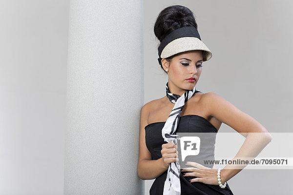 Junge Frau mit Hochsteckfrisur  Sonnenhut und schwarzem Kleid posiert vor Säule  Fashion