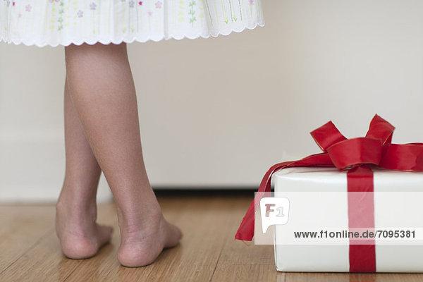 Mädchen neben dem Geschenk stehend  Unterteil  Rückansicht