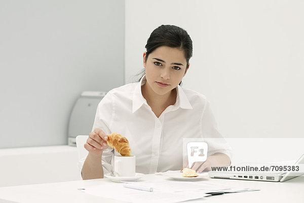 Junge Frau taucht Croissant in Kaffee am Schreibtisch im Büro ein