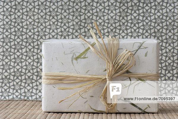 Geschenk verpackt in Papier und Raffia