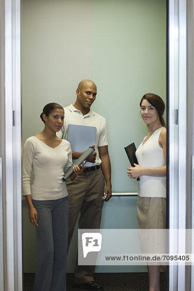 Junge Büroangestellte stehen im Aufzug