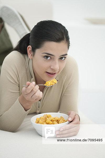 Junge Frau auf dem Bauch liegend  Schüssel mit Getreide essen