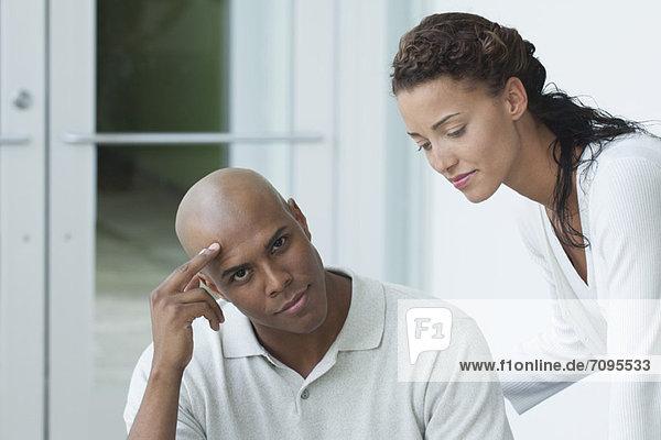 Junger Mann sitzt und schaut in die Kamera  junge Frau neigt zum jungen Mann