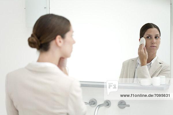 Frau schaut in den Spiegel und schminkt sich mit Puderquaste.