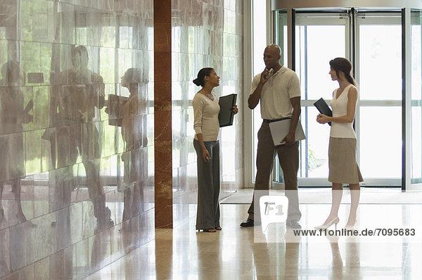 Kollegen sprechen in der Lobby  hinterleuchtet