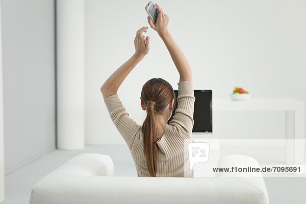 Frau beim Fernsehen mit erhobenen Armen  Rückansicht