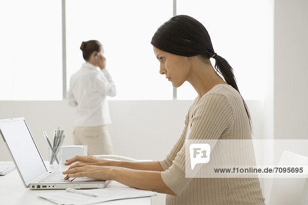 Junge schwangere Frau beim Tippen am Laptop im Büro  hintergrundbeleuchtet