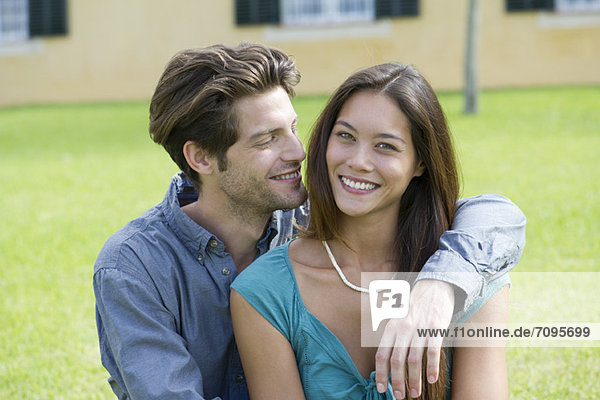 Young man with arm around girlfriend  portrait