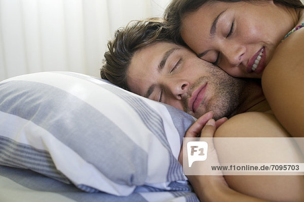 Junges Paar im Bett liegend mit geschlossenen Augen  abgeschnitten