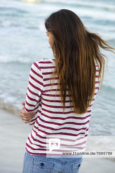 Junge Frau am Strand stehend  Rückansicht