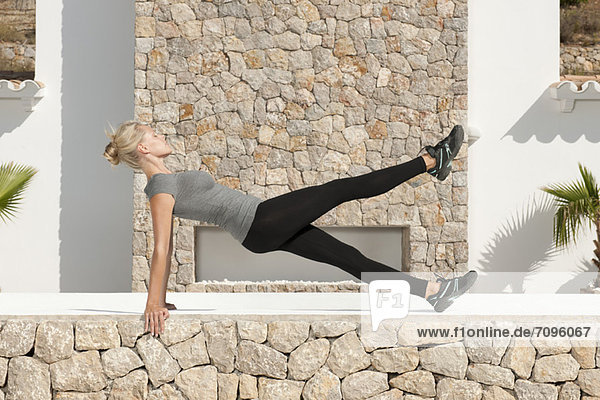 Young woman doing pilates exercise outdoors  eyes closed  side view