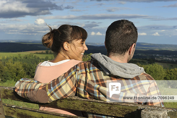 A young couple sitting on a bench  Hegaublick  Baden-Wuerttemberg  Germany  Europe  PublicGround