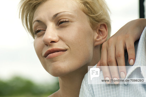 Young woman with hand on man's shoulder  looking away and smiling