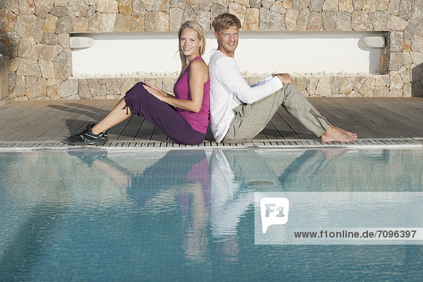 Young couple sitting back to back at poolside  portrait