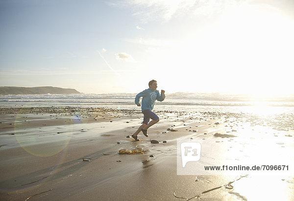 Junge läuft am Strand