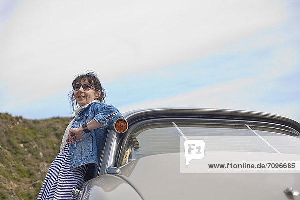 Ältere Frau  die sich auf das Auto stützt