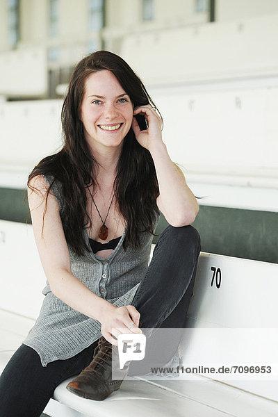 Lächelnde Frau auf der Bank sitzend
