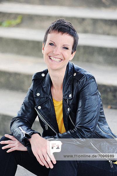Lächelnde Frau auf Stadttreppe sitzend