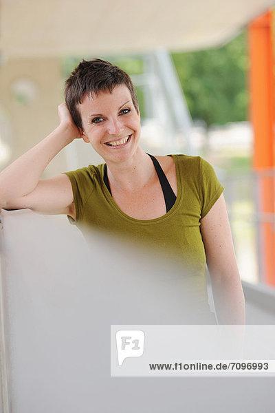 Lächelnde Frau  die sich an die Stange lehnt