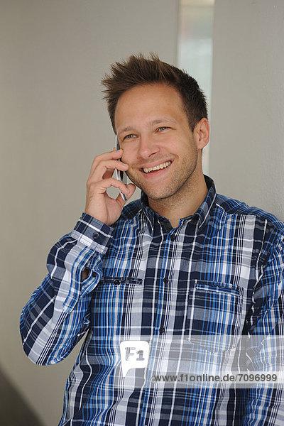 Lächelnder Mann spricht am Handy
