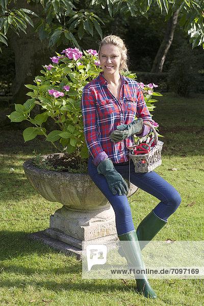 Frau trägt Blumentopf im Garten