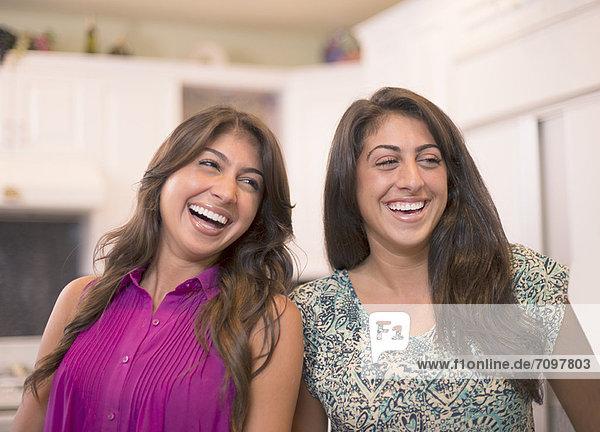 Schwestern lachen gemeinsam in der Küche